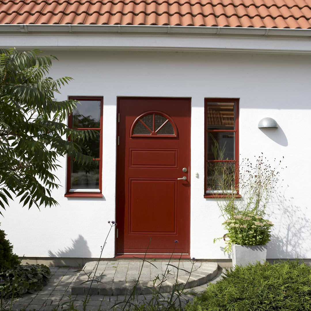 inngangspartiet på et hvit murhus med rød dør