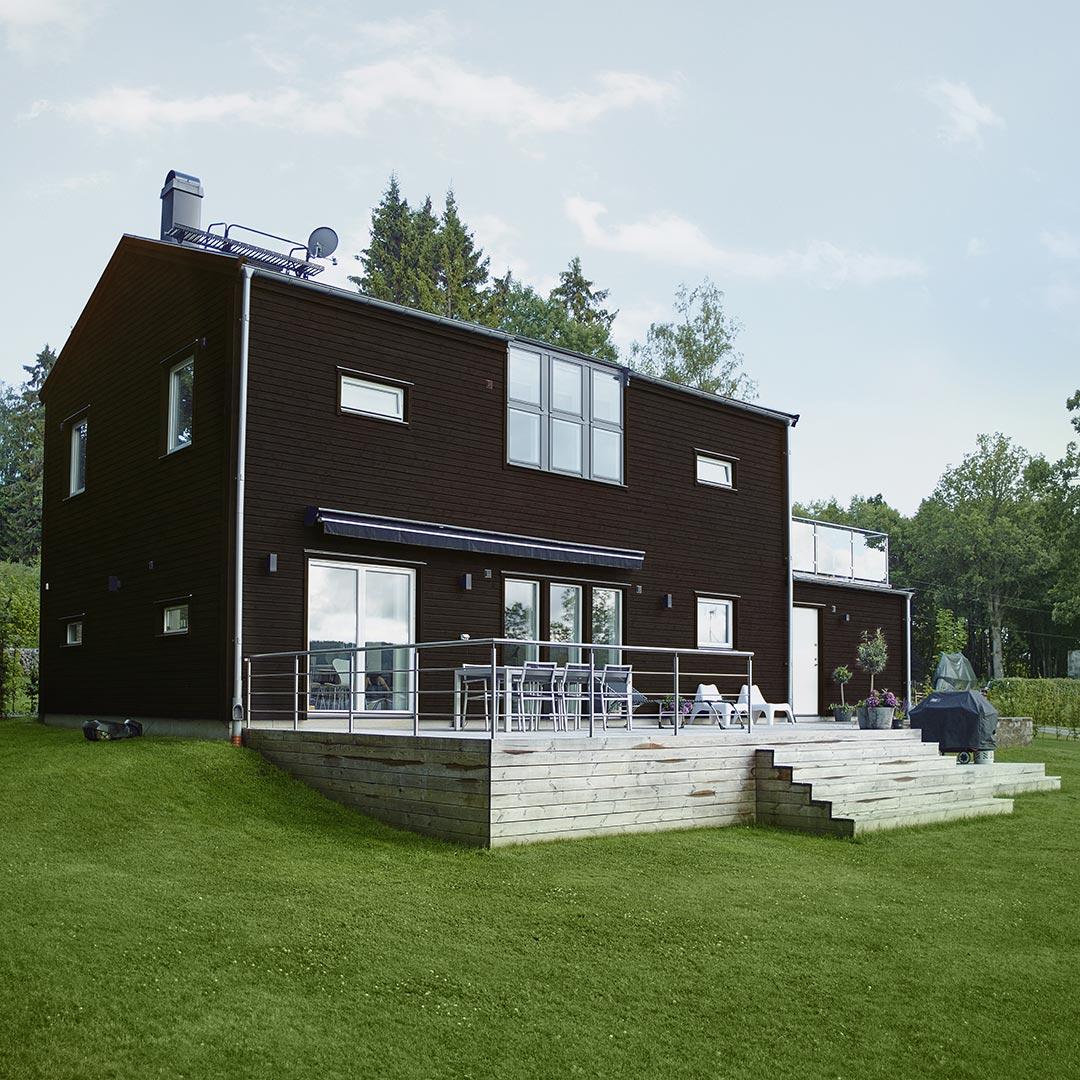 moderne hus i farge kakao med stor hage rundt