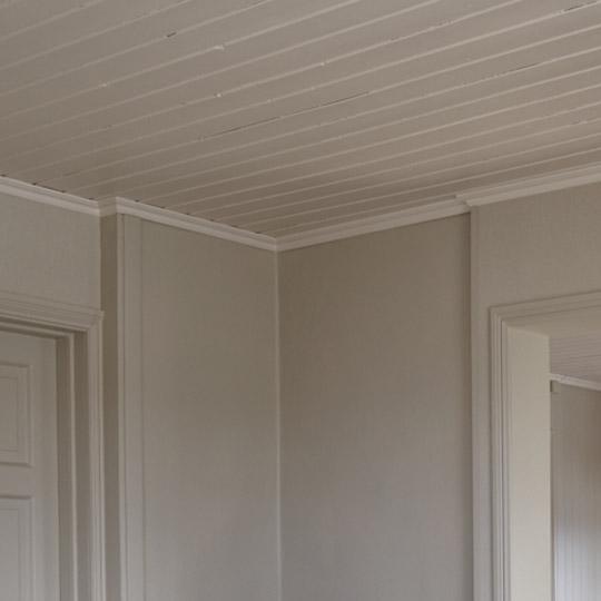 Nærbilde av et hjørne hvor tak er med malt panel og list i samme farge