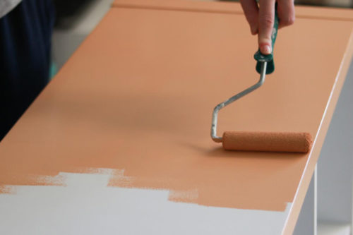Nærbilde av en som maler en ikea hylle med rulle