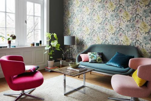 Stue med fargerike møbler, store vinduer og blomstrete tapet bak sofa