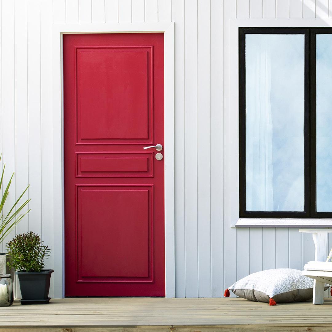 Inngangspartiet til et hus med rød nymalt ytterdør